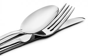 Cutlery - a spoon, fork and knife stacked up on a white background with space for text
